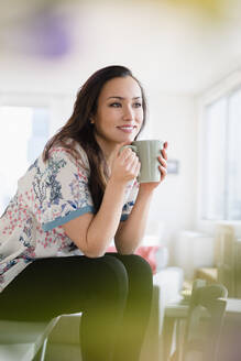 Woman drinking cup of coffee in living room - BLEF08706