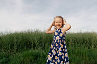 Portrait of happy little girl wearing summer dress with floral design - OGF00011