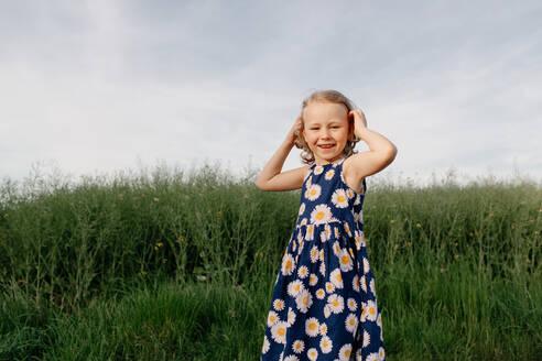 Portrait of happy little girl wearing summer dress with floral design - OGF00011