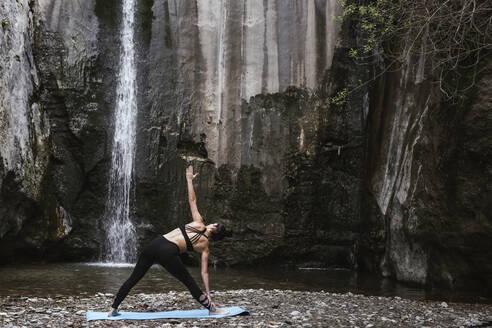 Woman practising yoga at waterfall, triangle pose - LJF00363
