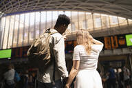 Back view of young couple looking at display panel of train station, London, UK - FBAF00853