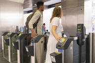 Young couple passing subway gate with electronic tickets - FBAF00856