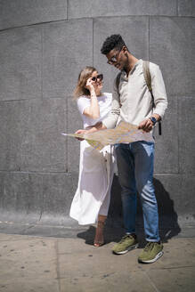 Young couple with city map, London, UK - FBAF00865