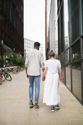 Back view of young couple walking hand in hand on pavement - FBAF00874