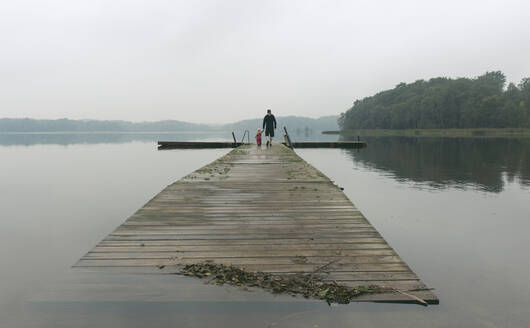 Father and a toddler daughter walking along a water platform on a lake, Sweden, Skåne County - IHF00172