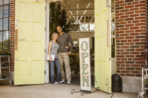 Couple standing in flower shop doorway - BLEF08786