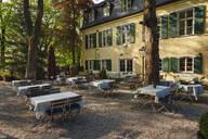 Germany, Upper Bavaria, Munich, Tables in garden ofGutshof Menterschwaige restaurant - SIE08739
