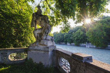 Germany, Upper Bavaria, Munich, St. Christopher's statue surrounded with trees by Isar river at sunset - SIEF08754