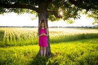 Portrait of little girl standing under apple tree with clover flowers in hands - LVF08138