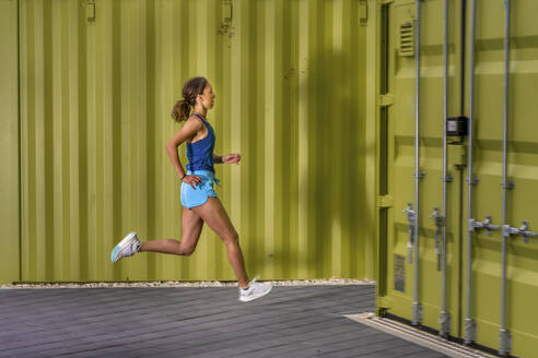 Young woman jogging on pavement in front of cargo containers - STSF02084