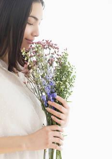 Hispanic woman smelling bouquet of flowers - BLEF08858