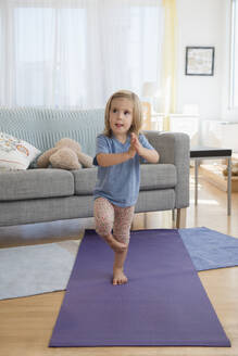 Caucasian girl practicing yoga in living room - BLEF08909
