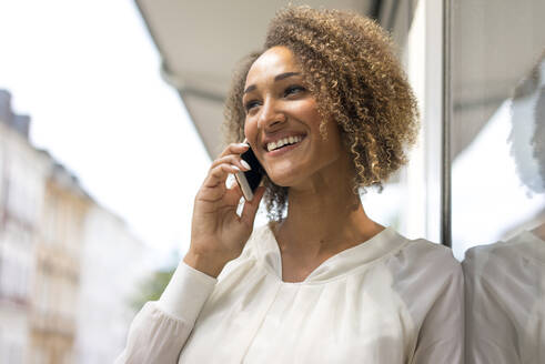 Portrait of happy young woman on the phone - MOEF02344