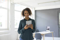 Portrait of smiling young businesswoman with digital tablet in office - MOEF02374