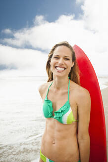 Caucasian woman on beach with surfboard - BLEF08956
