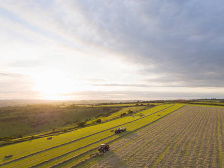 Aerial View Of Tractor Baling Hay In Field At Sunset - JUIF02169