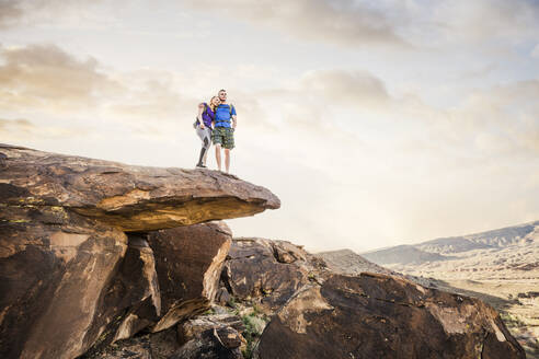 Caucasian couple on rock formation admiring landscape - BLEF09115