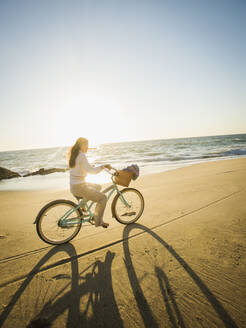 Mixed race woman riding bicycle on beach - BLEF09133