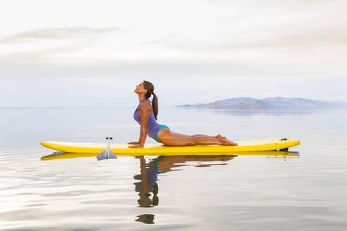 Filipino woman practicing yoga on paddle board - BLEF09139
