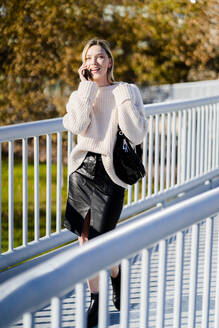 Smiling young woman on the phone walking on footbridge in autumn - GIOF06587
