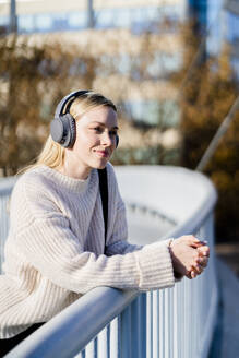 Portrait of content young woman leaning on railing of footbridge listening music with headphones - GIOF06590