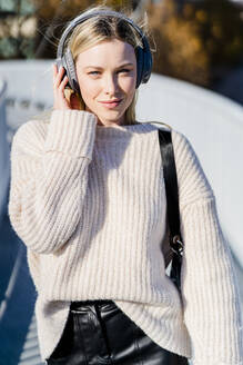 Portrait of content young woman listening music with headphones outdoors - GIOF06593