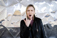 Portrait of screaming young woman showing Rock And Roll Sign - GIOF06602