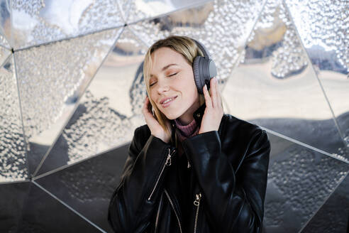 Portrait of smiling young woman with eyes closed listening music with wireless headphones - GIOF06605