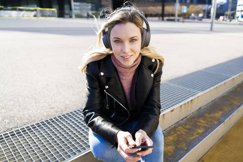 Portrait of young woman listening music with smartphone and headphones, Barcelona, Spain - GIOF06614