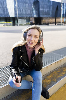 Portrait of young woman listening music with smartphone and headphones, Barcelona, Spain - GIOF06617