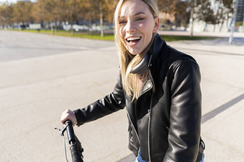 Portrait of laughing young woman  with kick scooter wearing black leather jacket - GIOF06620
