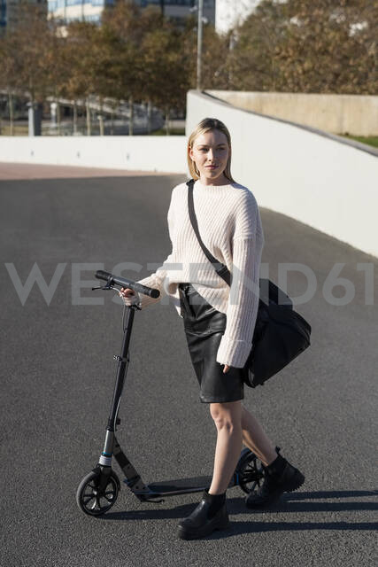 Young woman with sports bag and kick scooter on the street - GIOF06641 - Giorgio Fochesato/Westend61