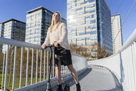 Blond young woman with kick scooter on footbridge - GIOF06653