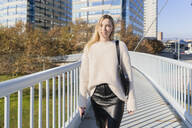 Portrait of blond young woman with smartphone walking on footbridge - GIOF06656