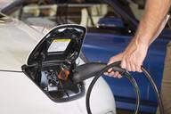 Close up of Caucasian man recharging electric car - BLEF09254