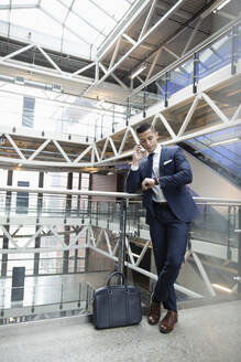 Young businessman talking on smart phone and checking the time on wristwatch on office atrium balcony - HEROF37009