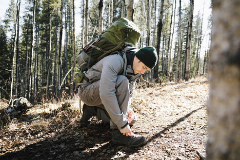 Man with backpack hiking, tying shoe in sunny woods - HEROF37126