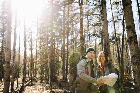 Couple with map and backpacks hiking in sunny woods - HEROF37129