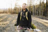 Portrait confident male volunteer planting trees in sunny woods - HEROF37153