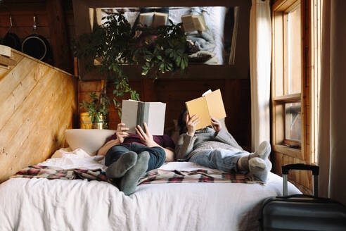 Couple relaxing, reading books on cabin bed - HEROF37168