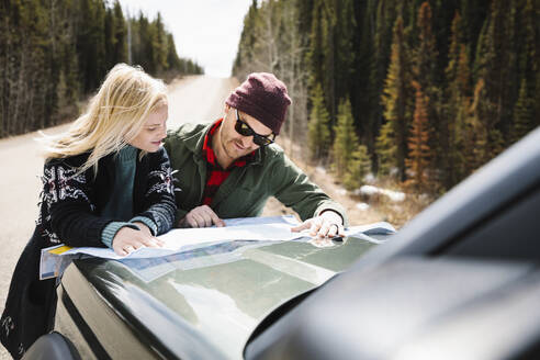 Couple looking at map on hood of car at sunny roadside - HEROF37192