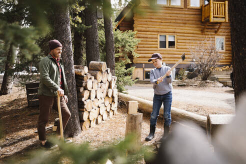 Father teaching son how to cut firewood outside cabin - HEROF37207