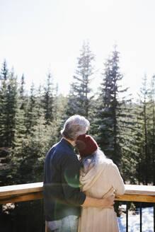 Affectionate couple hugging on sunny balcony overlooking woods - HEROF37243