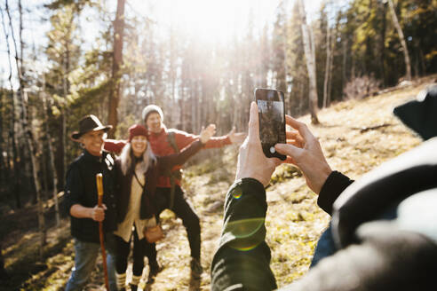 Man with camera phone photographing friends hiking in sunny woods - HEROF37249