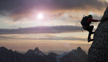 Caucasian climber scaling mountain in remote landscape - BLEF09387