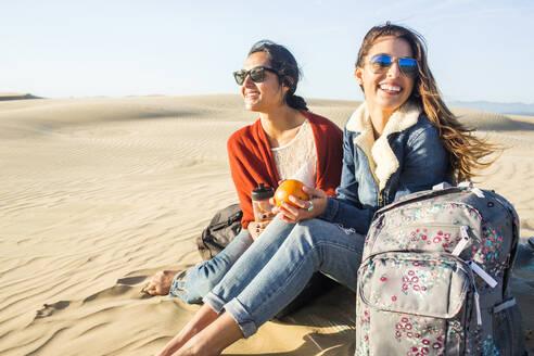 Mixed race women sitting on sand dunes - BLEF09414