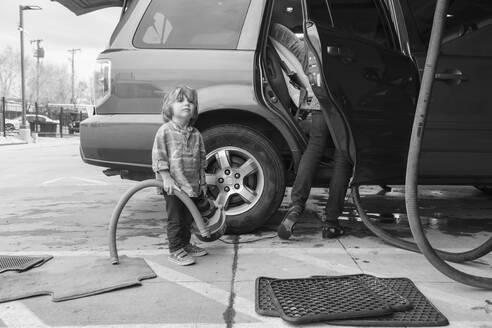 Caucasian preschooler boy helping clean car - BLEF09446