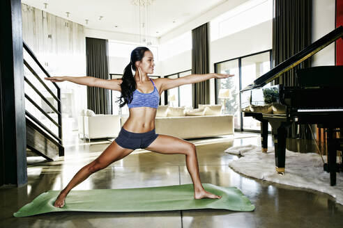 Chinese woman practicing yoga in living room - BLEF09449