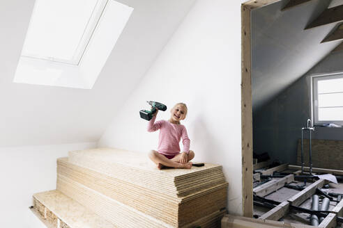 Portrait of a happy girl with electric drill in a home to be renovated - KMKF00992