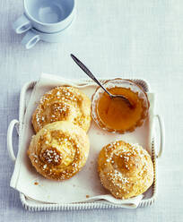Overhead view of homemade bread rolls with jam on tray - PPXF00198